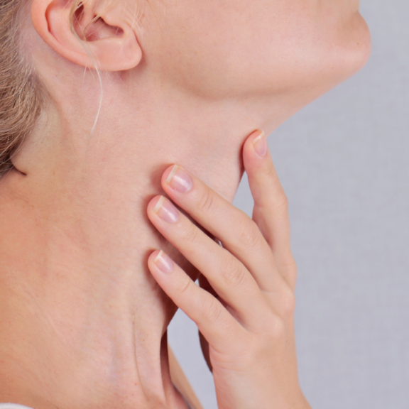 Femme touchant son cou pour illustrer les troubles de la thyroïde